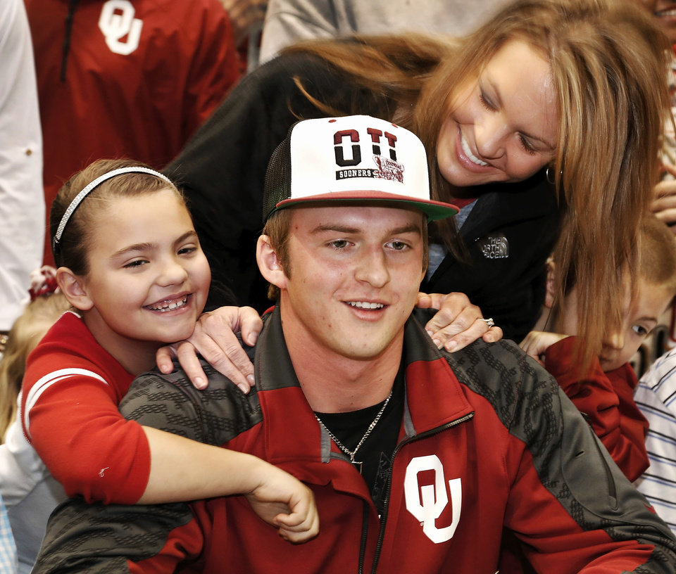 Photo - Justice Hansen gets hugs from his mom, Kara, and his sister, Acyn, 6, after he signed the letter. Justice Hansen is an Edmond Santa Fe quarterback who signed a letter of intent to play football with OU during signing day ceremony in the gymnasium at Edmond Santa Fe High School on Wednesday, Feb. 5, 2014.   Photo by Jim Beckel, The Oklahoman