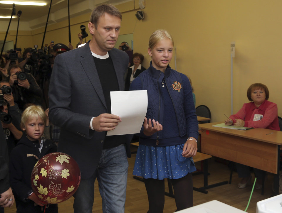 Photo - Russian opposition leader Alexei Navalny prepares to vote in Moscow's mayoral election in Moscow, Russia, Sunday, Sept. 8, 2013.  His daughter Daria is on right, and his son Zakhar is on left. (AP Photo/Sergei Grits)