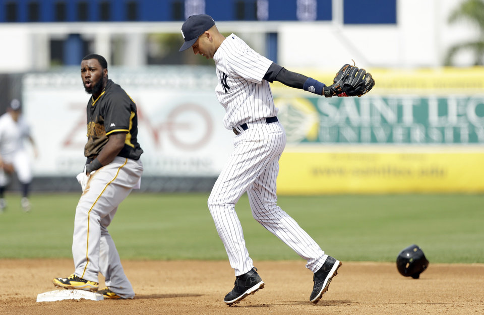 Photo - New York Yankees shortstop Derek Jeter reacts after tagging out Pittsburgh Pirates' Josh Harrison, left, during a stolen base attempt in the fifth inning of an exhibition baseball game Thursday, Feb. 27, 2014, in Tampa, Fla. (AP Photo/Charlie Neibergall)