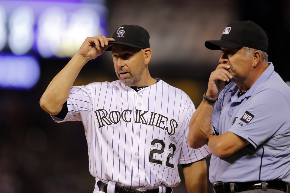 Photo - Umpire Dale Scott listens as Colorado Rockies manager Walt Weiss questions a call at first during the sixth inning of a baseball game against the Cincinnati Reds on Friday, Aug. 15, 2014, in Denver. (AP Photo/Jack Dempsey)