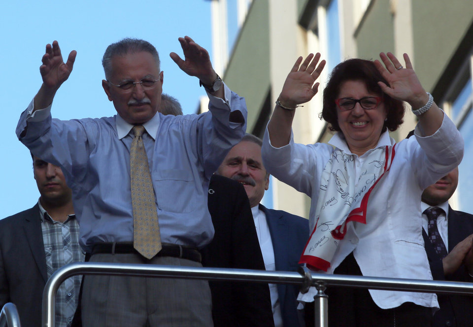 Photo - Ekmeleddin Ihsanoglu, and his wife Fusun gesture to supporters, during a rally, in Istanbul, Turkey, Saturday, Aug. 9, 2014. Some 53 million Turks go the polls on Sunday to choose their 12th president in an election considered a turning point for the country of 76 million people, with Prime Minister Recep Tayyip Erdogan vying for the position he has pledged to transform from a symbolic role into a position of power. Ekmeleddin Ihsanoglu, the former chief of the Organization of Islamic Cooperation, and Kurdish politician Selahattin Demirtas are also running. (AP Photo/Volkan Yildirim)
