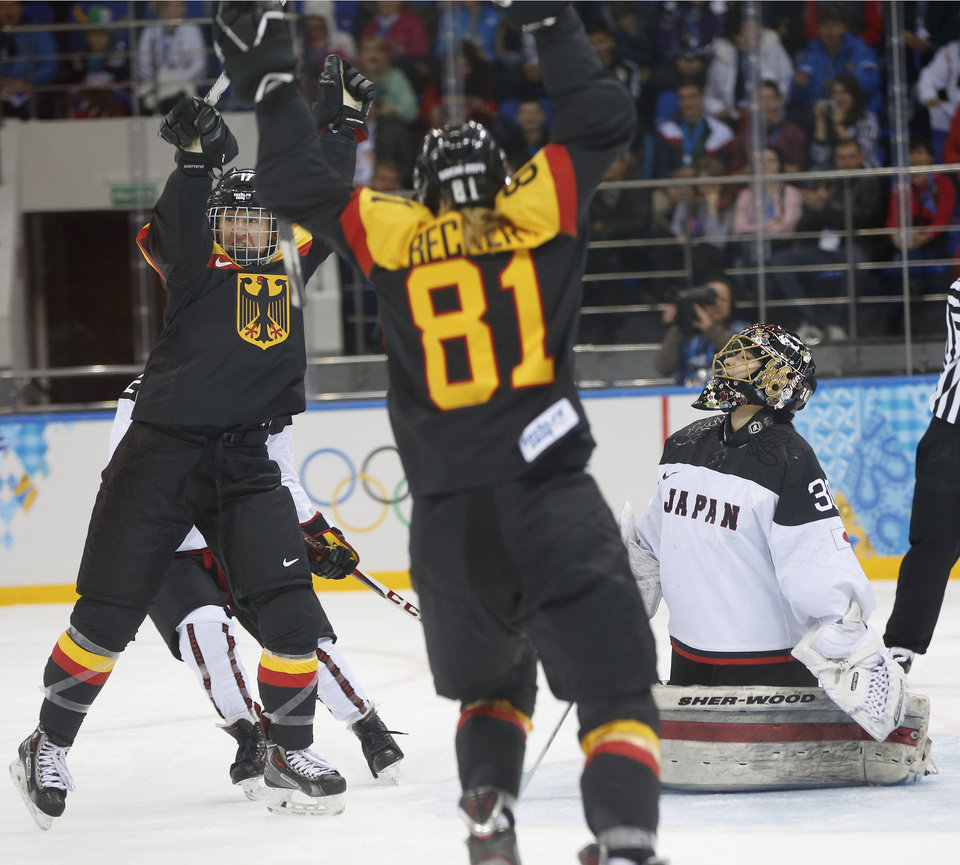 Photo - Goalkeeper Nana Fujimoto of Japan looks up as Team Germany celebrates Manuela Anwander's goal during the first period of the 2014 Winter Olympics women's ice hockey game at Shayba Arena, Thursday, Feb. 13, 2014, in Sochi, Russia. (AP Photo/Petr David Josek)