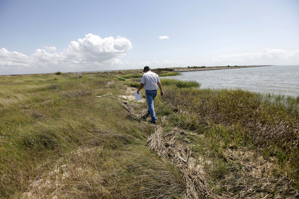 FILE - In this Tuesday, June 28, 2011 file photo, Scott Alford, a soil conservationist for the Natural Resources Conservation Service, walks along the banks of a manmade marsh, a creation dredged from the Houston Ship Channel near Baytown, Texas. The marsh is part of a  project to restore lost wetlands and islands off the Texas coast. A report released to The Associated Press says the Natural Resources Conservation Service has already committed more than a half-billion dollars to the Gulf Coast in the past two years, nearly one-fifth of it on projects directly linked to recovery from the 2010 oil spill.(AP Photo/David J. Phillip, File)