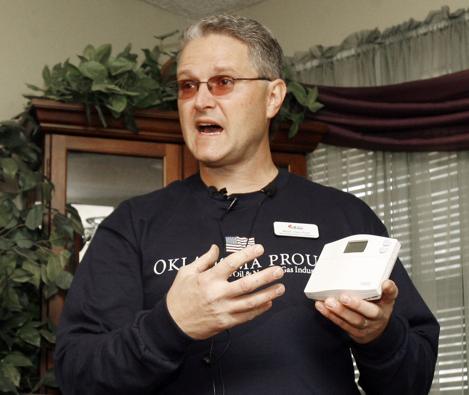 Photo - Matt Van Horn discusses the benefits of a programmable thermostat, as the Oklahoma Energy Resources Board and state Commerce Department perform a weatherization demonstration at a home in NE Oklahoma City, OK, Tuesday, Nov. 20, 2007. By Paul Hellstern / The Oklahoman ORG XMIT: KOD
