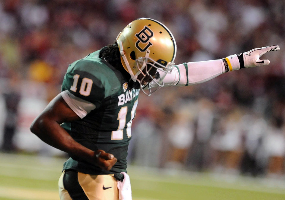 Baylor quarterback Robert Griffin III reacts to a Terrance Ganaway touchodwn over Oklahoma during an NCAA college football game, Saturday, Nov. 19, 2011, in Waco, Texas. (AP Photo/Waco Tribune Herald, Rod Aydelotte)