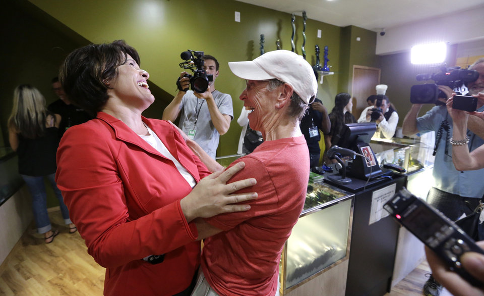 Photo - Alison Holcomb, left, criminal justice director at the Washington state ACLU, shares a laugh with Deb Greene the first customer at Cannabis City, on the first day that sales of recreational pot became legal in the state Tuesday, July 8, 2014, in Seattle.  Washington on Tuesday became the second state to allow people to buy marijuana legally in the U.S. without a doctor's note as eager customers who lined up outside stores made their purchases and savored the moment. (AP Photo/Elaine Thompson, Pool)