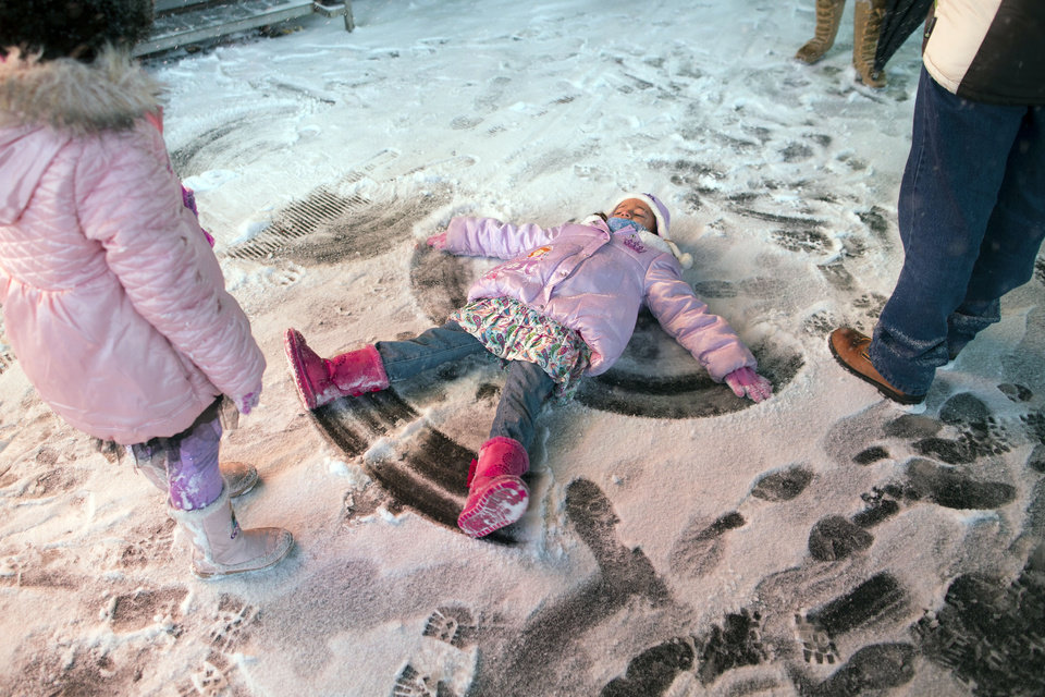 Photo - A child makes a snow angel in Times Square, Thursday, Jan. 2, 2014, in New York. The snow storm is expected to bring snow, stiff winds and punishing cold into the Northeast. (AP Photo/John Minchillo)