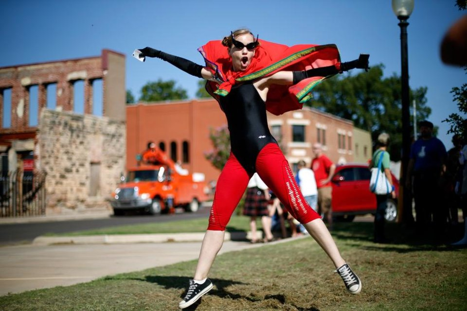Photo -  Jennifer Engleman from Norman, dressed as Firefly, poses as her friend takes a photo during International Superhero Day in Pauls Valley, Okla., Saturday, August 4, 2012.