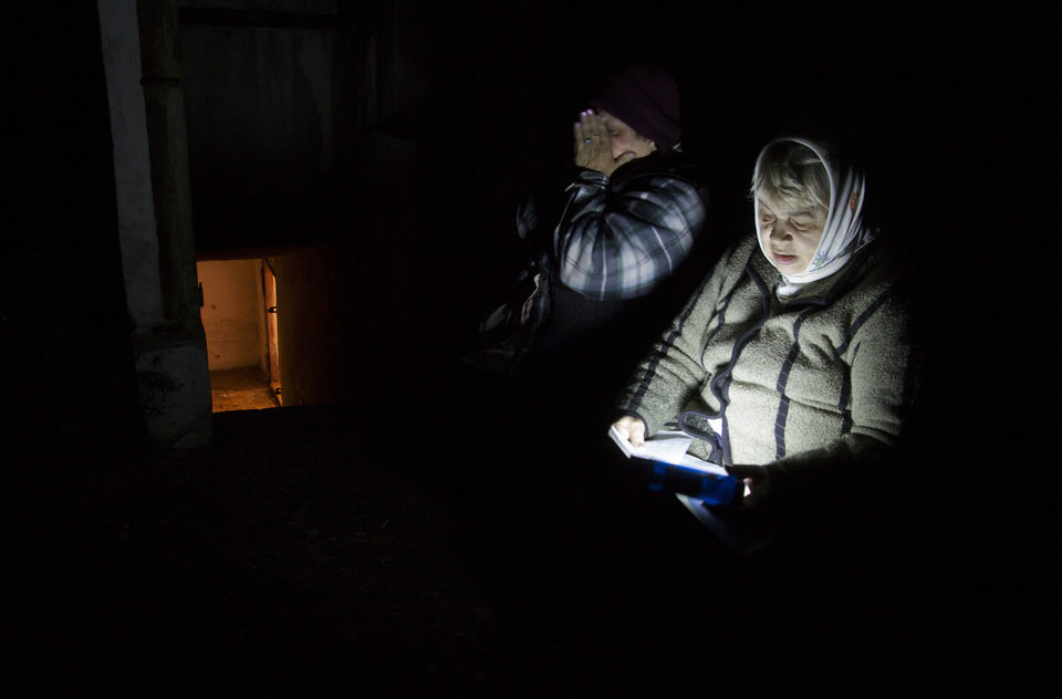 Photo - Local resident Galina Dudkina, right, reads poems near an entrance to a bomb shelter, as she and her neighbour go out for fresh air, during a short cease fire, in the Petrovsky of Donetsk, eastern Ukraine Tuesday, Aug. 5, 2014. (AP Photo/Dmitry Lovetsky)