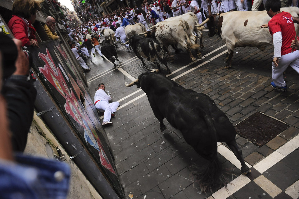 Photo - A reveler falls in front of a ''Torrestrella'' fighting bull on Estafeta corner during the running of the bulls at the San Fermin festival, in Pamplona, Spain, Monday, July 7, 2014. Revelers from around the world arrive to Pamplona every year to take part in some of the eight days of the running of the bulls glorified by Ernest Hemingway's 1926 novel