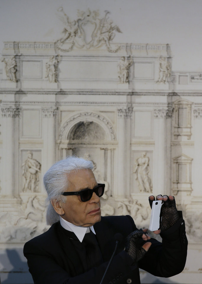 Photo - Designer Karl Lagerfeld takes a picture with his mobile phone backdropped by a drawing of Trevi's fountain during a press conference, in Rome, Monday, Jan. 28, 2013. The Fendi fashion house is financing an euro 2.12 million ($2.8 million) restoration of Trevi Fountain in Rome, famed as a setting for the film