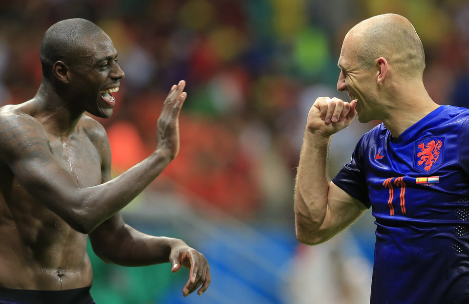 Photo - Netherlands' Bruno Martins Indi, left, and Netherlands' Arjen Robben celebrate after the group B World Cup soccer match between Spain and the Netherlands at the Arena Ponte Nova in Salvador, Brazil, Friday, June 13, 2014.  The Netherlands won the match 5-1. (AP Photo/Bernat Armangue)
