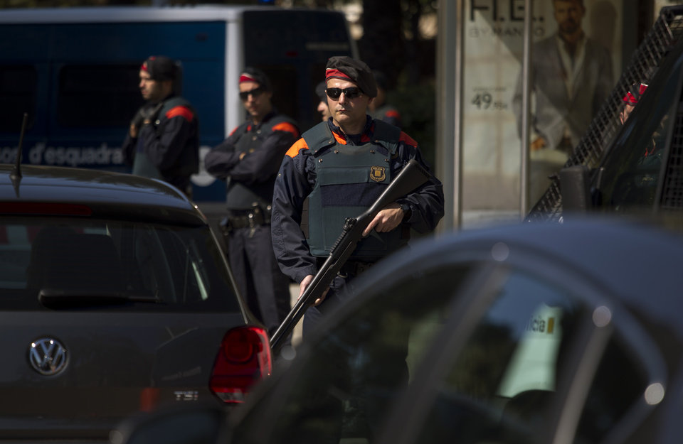 Photo -   A police officer hold a weapon in a checkpoint near the hotel where the meeting of the European Central Bank is taking place in Barcelona, Spain, Thursday, May 3, 2012. European stocks pushed ahead Thursday after cash-strapped Spain got through another set of bond auctions unscathed and ahead of the latest policy statement from the European Central Bank's president Mario Draghi. (AP Photo/Emilio Morenatti)