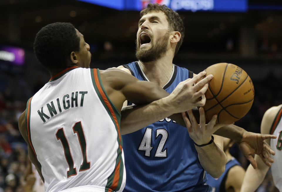 Milwaukee Bucks' Brandon Knight (11) fouls Minnesota Timberwolves' Kevin Love (42) during the first half of an NBA basketball game, Saturday, Dec. 28, 2013, in Milwaukee. (AP Photo/Jeffrey Phelps)