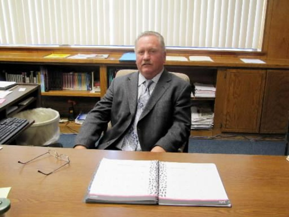 Photo - New Lima Superintendent Gil Turpin sits behind his desk. Turpin leads a student population of 266 students in one of 10 school districts in Seminole County about 60 miles east of Oklahoma City. Photo by Sarah Boswell, The Oklahoman