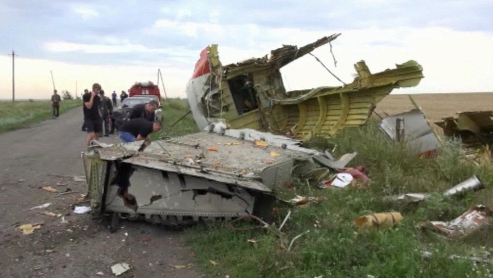 Photo - In this image taken from video, Thursday July 17, 2014,  showing part of the wreckage of a passenger plane carrying 295 people after it was shot down Thursday as it flew over Ukraine, near the village of Hrabove, in eastern Ukraine. Malaysia Airlines tweeted that it lost contact with one of its flights as it was traveling from Amsterdam to Kuala Lumpur over Ukrainian airspace.(AP Photo / Channel 1) RUSSIA OUT - TV OUT