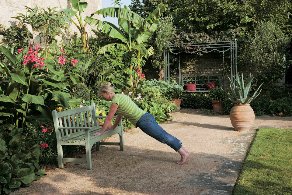 "This undated publicity photo released by courtesy Timber Press, shows Bunny Guinness using a garden bench for exercise from the book, ""Garden Your Way To Health and Fitness,"" by Bunny Guinness and Jacqueline Knox (Design, Bunny Guinness). Gardens can be pathways to better conditioning, when you trade treadmills for trails, exercise mats for lawns and garden benches for weight racks. (AP Photo/Courtesy Timber Press)"