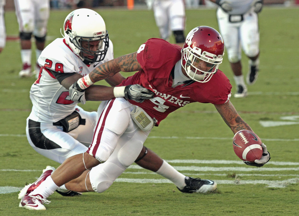 Oklahoma Sooners' Kenny Stills (4) tries to stretch out a run after catch as Ball State Cardinals' Andre Dawson (28) holds on during the first half of the college football game between the University of Oklahoma Sooners (OU) and the Ball State Cardinals at Gaylord Family-Oklahoma Memorial Stadium on Saturday, Oct. 1, 2011, in Norman, Okla. Photo by Steve Sisney, The Oklahoman