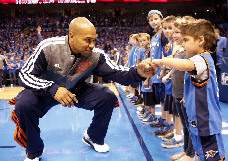 Photo - Oklahoma City's Derek Fisher (6) fist bumps Drew Kent, 3, of Edmond before Game 5  in the first round of the NBA playoffs between the Oklahoma City Thunder and the Houston Rockets at Chesapeake Energy Arena in Oklahoma City, Wednesday, May 1, 2013. Photo by Sarah Phipps, The Oklahoman