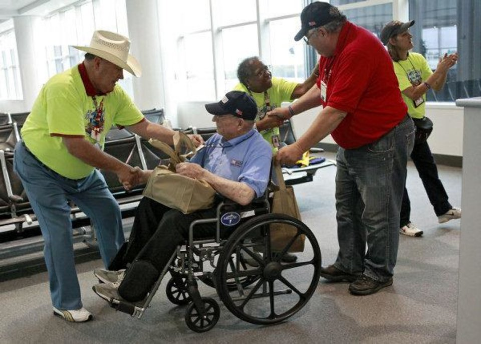 Photo - Gus Oliver, a veteran from Tulsa, and his son Gus Oliver Jr., are greeted by members of the Honor Flight Network's Baltimore Ground Crew as they arrive at Baltimore Washington International Airport on Wednesday, Oct. 12, 2011. Veterans from Oklahoma visited the National WWII Memorial during an Oklahoma Honor Flight to Virginia and Washington D.C. Photo by John Clanton, The Oklahoman ORG XMIT: KOD
