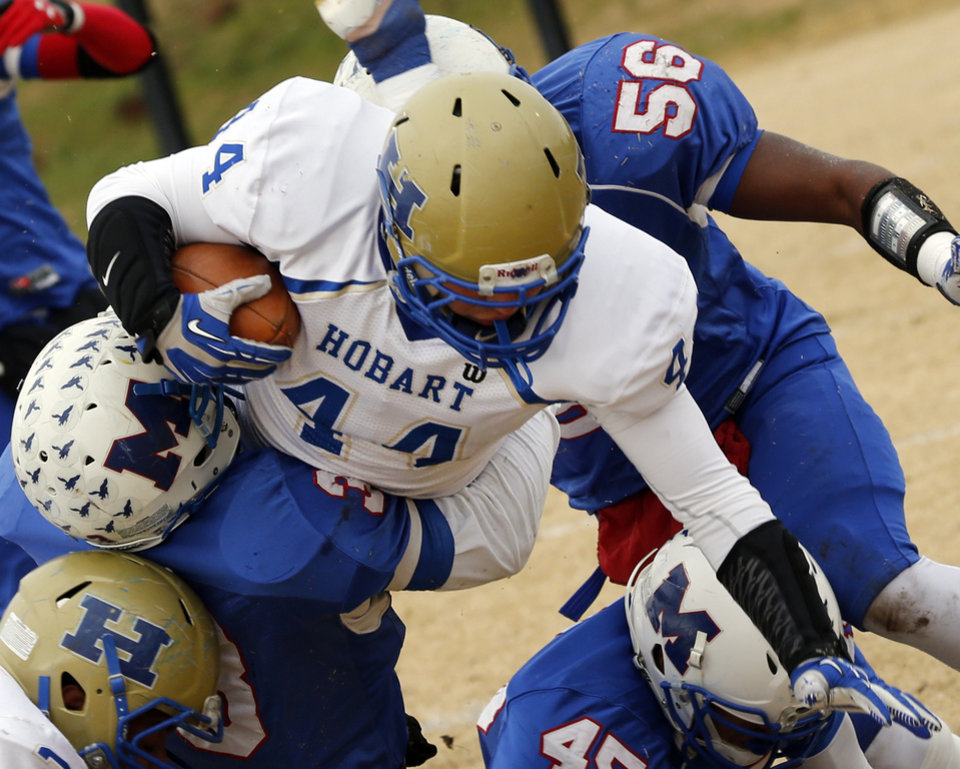 Photo - Hobart's Aaron Hernandez (44) tries to leap over the tackle of Millwood's Cameron Batson in high school football playoff action on Saturday, Nov. 23, 2013, in Oklahoma City, Okla. Photo by Steve Sisney, The Oklahoman