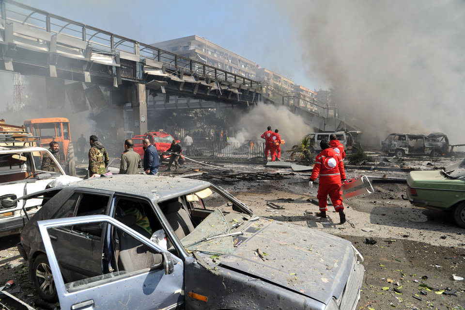 Photo - This photo released by the Syrian official news agency SANA, shows first responders working after a huge explosion that shook central Damascus, Syria, Thursday, Feb. 21, 2013. A car bomb shook central Damascus on Thursday, exploding near the headquarters of the ruling Baath party and the Russian Embassy, eyewitnesses and opposition activists said. (AP Photo/SANA)