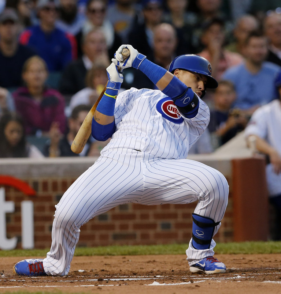 Photo - Chicago Cubs' Javier Baez ducks a high pitch from Milwaukee Brewers' Kyle Lohse during the first inning of a baseball game Wednesday, Aug. 13, 2014, in Chicago. (AP Photo/Charles Rex Arbogast)