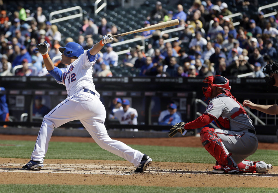 Photo - New York Mets' Juan Lagares hits a sacrifice fly during the first inning of the baseball game against the Washington Nationals at Citi Field, Thursday, April 3, 2014 in New York. (AP Photo/Seth Wenig)
