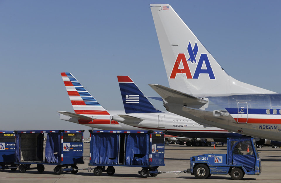 U.S. Airways and American Airlines planes are shown at gates at DFW International Airport Thursday, Feb. 14, 2013, in Grapevine, Texas. The two airlines will merge forming the world\'s largest airlines. (AP Photo/LM Otero)