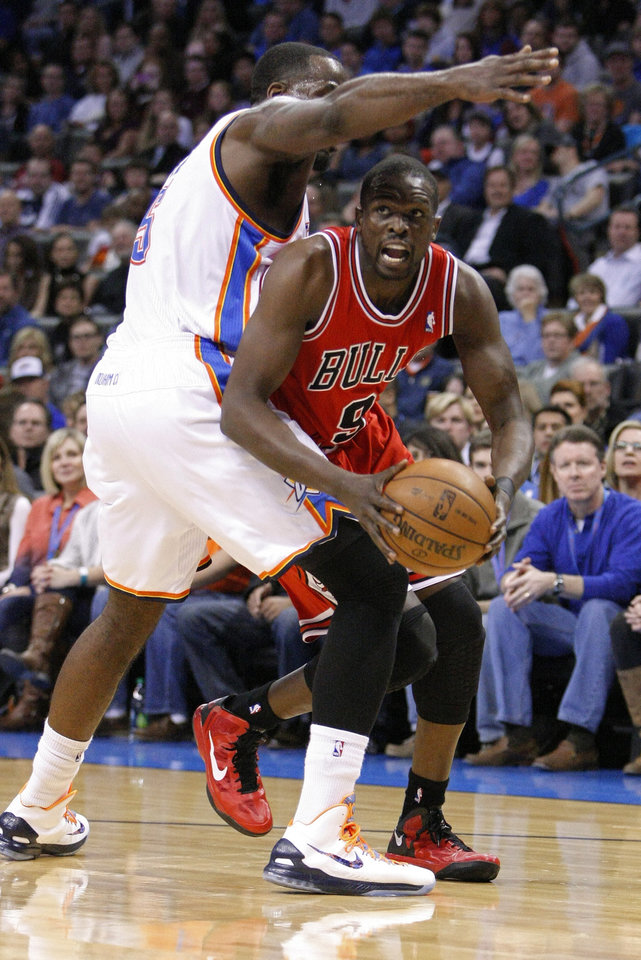 Oklahoma City Thunder center Kendrick Perkins, left, defends as Chicago Bulls forward Luol Deng, right, drives to the basket during the first quarter of an NBA basketball game in Oklahoma City, Sunday, Feb. 24, 2013. (AP Photo/Alonzo Adams)