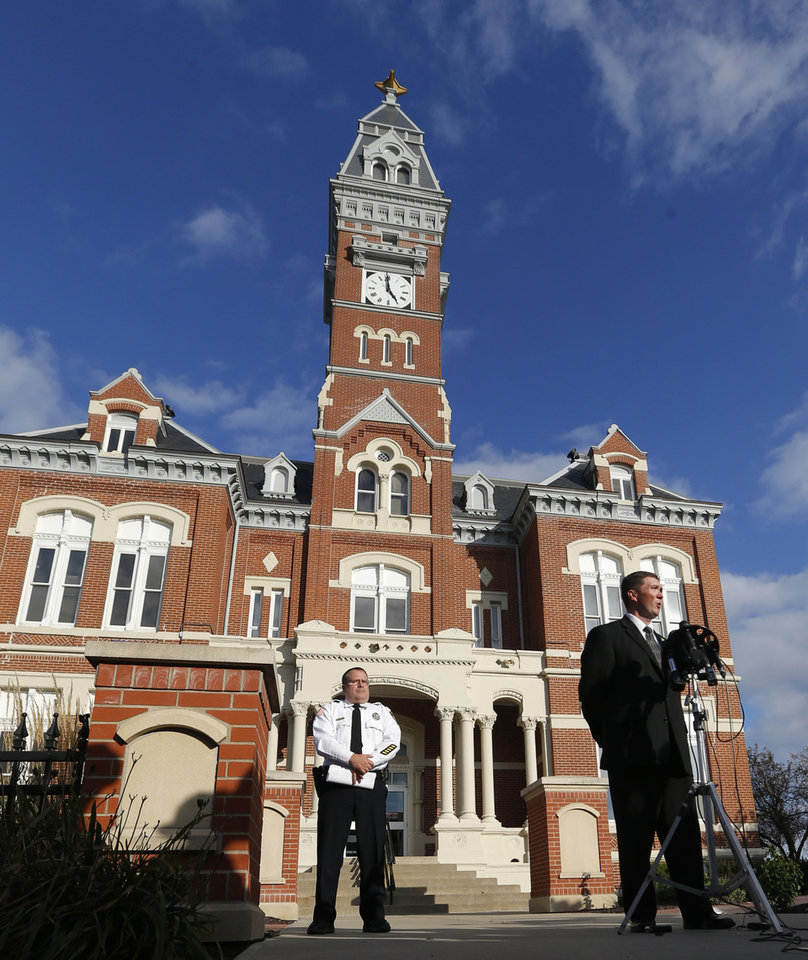 Photo - County prosecutor Robert Rice, right, and Sheriff Darren White hold a news conference outside the Nodaway County Court House in Maryville, Mo., Wednesday, Oct. 16, 2013. (AP Photo/Orlin Wagner)