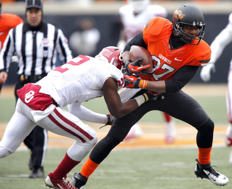 Photo - Oklahoma State's Tracy Moore (87) tries to get past Oklahoma's Julian Wilson (2) during the Bedlam college football game between the Oklahoma State University Cowboys (OSU) and the University of Oklahoma Sooners (OU) at Boone Pickens Stadium in Stillwater, Okla., Saturday, Dec. 7, 2013. Photo by Chris Landsberger, The Oklahoman