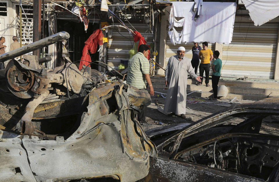 Photo - Civilians look at damage from a Saturday car bomb attack near a Kebab restaurant, in the mainly Shiite Habibiya neighborhood of Baghdad, Iraq, Sunday, May 11, 2014. A series of bombings on Saturday in Iraq killed and wounded scores of people, a day after army shelling killed many civilians and gunmen in the militant-held city of Fallujah, authorities said. (AP Photo/Karim Kadim)