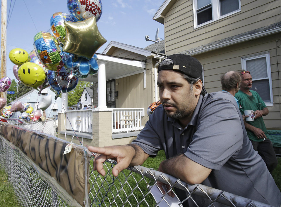 Photo - Ricardo DeJesus talks about his sister Gina at the family home Tuesday, May 7, 2013, in Cleveland. Police said Gina DeJesus and two other women who went missing separately about a decade ago were found in a house near downtown Cleveland Monday and likely had been tied up during years of captivity. Three brothers have been arrested. (AP Photo/Tony Dejak)