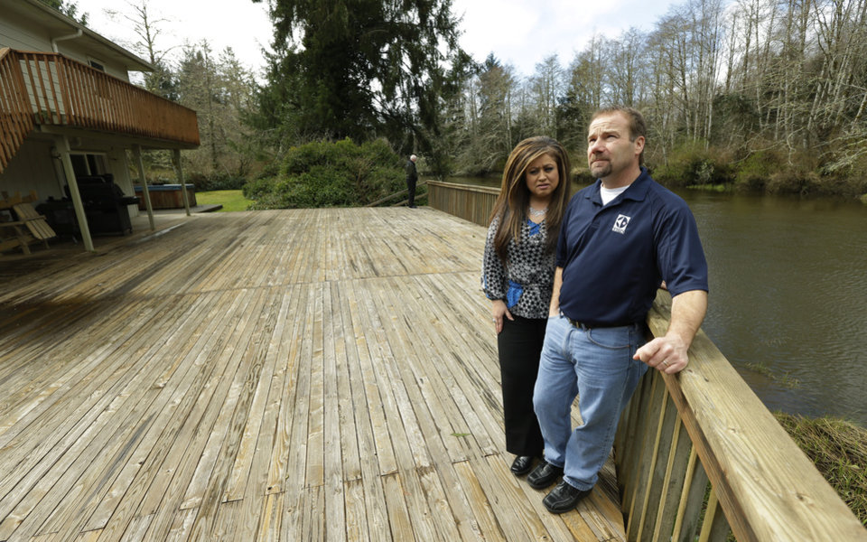 Photo - Darrin Moir, right, and his wife Leonor Moir, stand Monday, March 18, 2014 on the deck of their house, which is located along the Little Hoquiam River in Hoquiam, Wash. The Moirs currently pay about $1,700 annually for flood insurance, even though they say they have never had a major flooding incident since buying their home in 1996. Possible rate increases could up their premiums to more than $9,000 a year, which they say could prevent them from eventually selling their home. (AP Photo/Ted S. Warren)