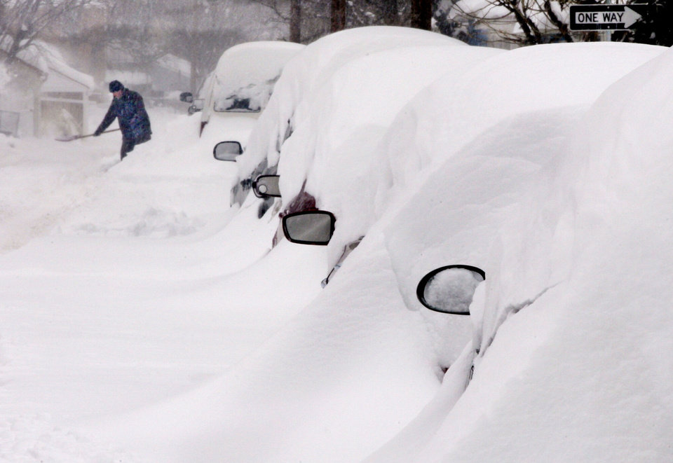 Photo - Snow covers a line of vehicles as a man digs out during a winter snow storm Thursday, Feb. 13, 2013, i n Winchester, Va. (AP Photo/The Winchester Star, Scott Mason)
