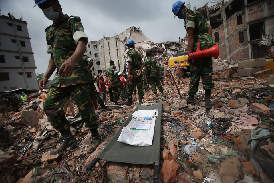 Photo - A stretcher with a body bag is placed on standby while workers toil in the collapsed garment factory building Tuesday April 30, 2013 in Savar, near Dhaka, Bangladesh. Emergency workers hauling large concrete slabs from a collapsed 8-story building said Tuesday they expect to find many dead bodies when they reach the ground floor, indicating the death toll will be far more than the official 386. One estimate said it could be as high as 1,400. The illegally constructed, 8-story Rana Plaza collapsed on the morning of April 24, bringing down the five garment factories inside.(AP Photo/Wong Maye-E)