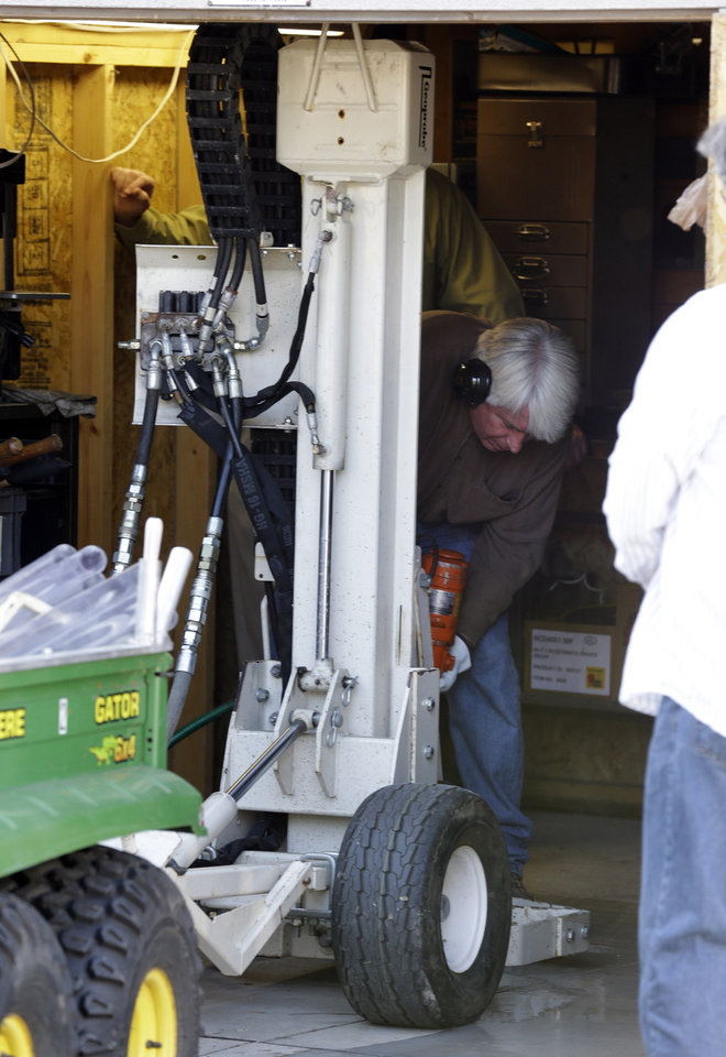 Photo -   FILE- In a Sept. 28, 2012 file photo authorities drill for soil samples in the floor of a shed at a Roseville, Mich., home Friday, Sept. 28, 2012. Police have been told by a source that former Teamsters boss Jimmy Hoffa may be buried beneath a driveway. Like many others that came before it, the latest search for Hoffa has come up empty. Tests on soil samples gathered last week from a backyard in suburban Detroit showed no traces that Hoffa — or anyone else — was buried there, Roseville police announced Tuesday, Oct. 2. (AP Photo/Paul Sancya, FILE)
