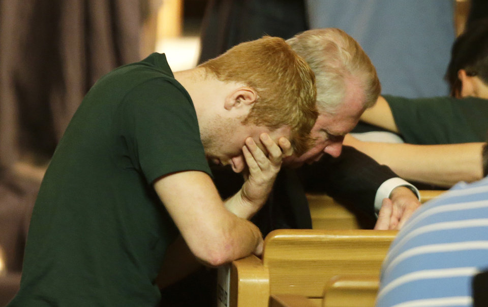 Photo - Seattle Mayor Ed Murray, right, kneels in prayer with an unidentified student during a prayer service Friday, June 6, 2014, at the First Free Methodist Church at Seattle Pacific University in Seattle. The service was held in response to a fatal shooting at the college Thursday afternoon. (AP Photo/Ted S. Warren)