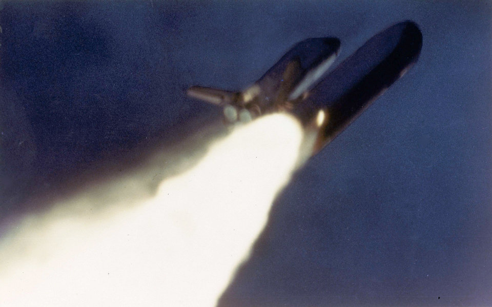 Photo - This Jan. 28, 1986, picture provided by NASA shows an unusual flame jutting from the side of a solid rocket booster on the space shuttle Challenger during its launch from the Kennedy Space Center in Cape Canaveral, Fla. A subsequent explosion killed its crew of seven. (AP Photo/NASA)