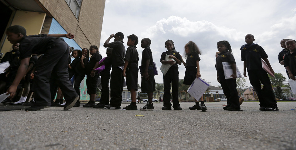 Photo - Students wait in line at ReNEW SciTech Academy, a charter school in New Orleans, Thursday, Aug. 14, 2014. Nine years after Hurricane Katrina, charter schools are the new reality of public education in New Orleans. The vast majority of public school students will be attending a charter school established by a state-run school district created in the wake of the storm. (AP Photo/Gerald Herbert)