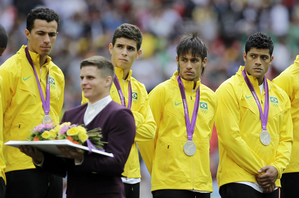 Photo -   Brazil players react on the podium as they receive the silver medal during a ceremony following their loss to Mexico in the men's soccer final at the 2012 Summer Olympics, Saturday, Aug. 11, 2012, in London. (AP Photo/Hussein Malla)