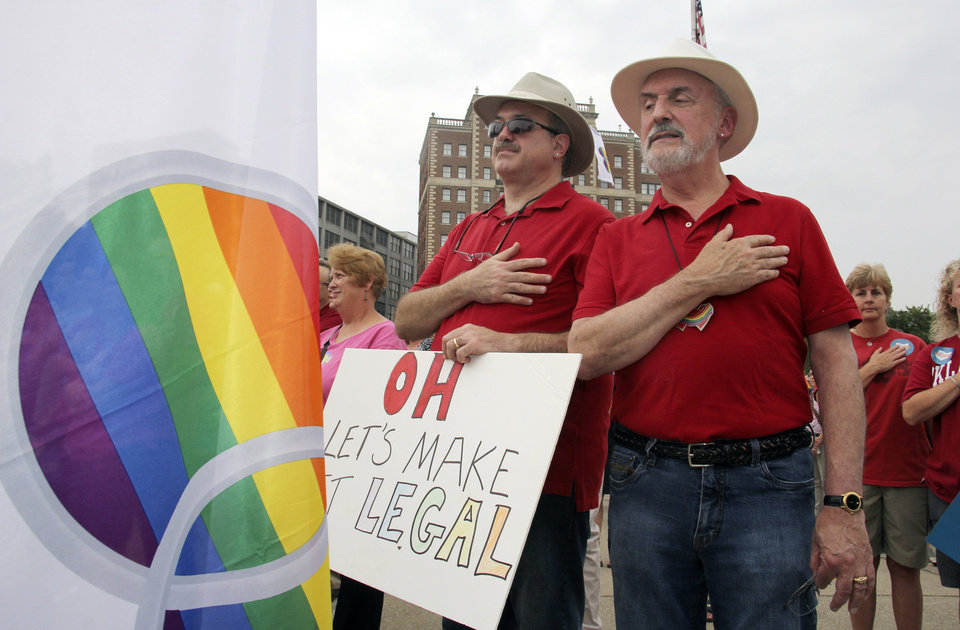Photo - Gay marriage supporters Duane Lewis and Rex Van Alstine, right, hold their hands to their chest as the national anthem plays during a rally in support of gay marriage in downtown Cincinnati, Tuesday, Aug. 5, 2014. The Cincinnati-based 6th U.S. Circuit Court of Appeals will hear arguments in six gay marriage fights from Ohio, Michigan, Kentucky and Tennessee on Wednesday, setting the stage for one ruling. (AP Photo/Tom Uhlman)