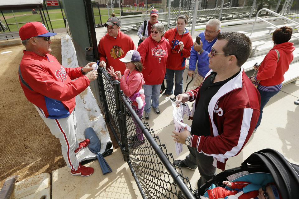 Photo - Philadelphia Phillies manager Ryne Sandberg, left, signs autographs for fans during spring training baseball practice Thursday, Feb. 13, 2014, in Clearwater, Fla. (AP Photo/Charlie Neibergall)