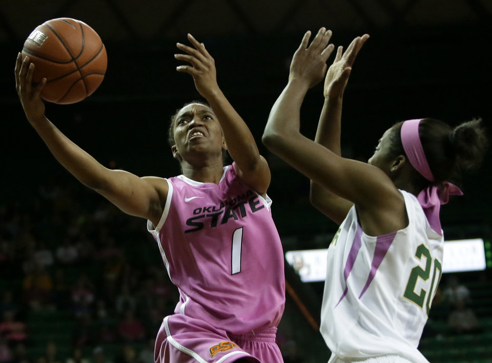 Photo - Oklahoma State 's Brittany Atkins (1) goes up to shoot as Baylor's Imani Wright (20) defends in the first half of an NCAA college basketball game on Sunday, Feb. 9, 2014, in Waco, Texas. Both teams wore uniforms accented with pink for breast cancer awareness. (AP Photo/Tony Gutierrez)