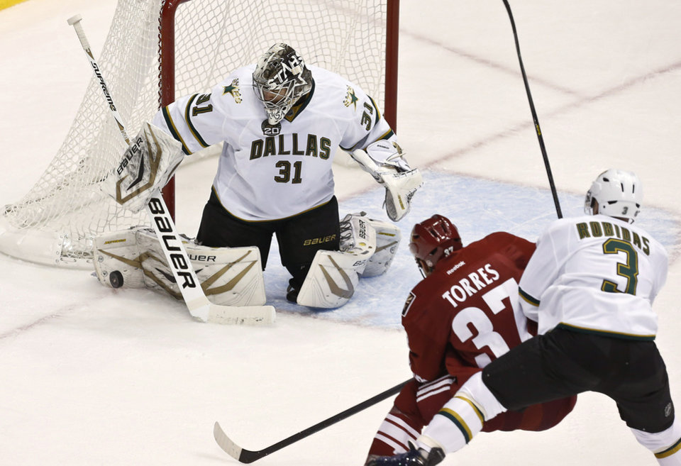 Dallas Stars' Richard Bachman (31) makes a save on a shot by Phoenix Coyotes' Raffi Torres (37) as Stars' Stephane Robidas (3) defends during the second period in an NHL hockey game Saturday, Feb. 2, 2013, in Glendale, Ariz. (AP Photo/Ross D. Franklin)