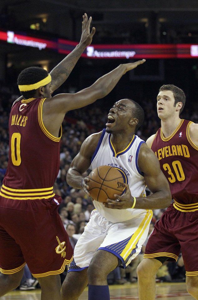 Golden State Warriors power forward Carl Landry, center, is defended by Cleveland Cavaliers small forward C.J. Miles (0) and power forward Jon Leuer (30) during the third quarter of an NBA basketball game in Oakland, Calif., Wednesday, Nov. 7, 2012. The Warriors won 106-96. (AP Photo/Jeff Chiu)