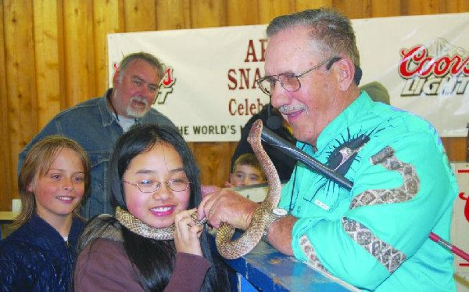 Photo - Ron Orf shows a snake to a girl during a demonstration.  Provided by Joye Wright, The Apache News
