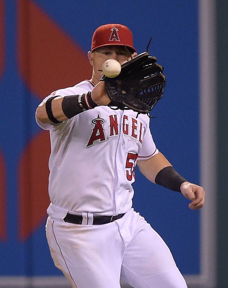Photo - Los Angeles Angels right fielder Kole Calhoun fields a ball hit for an RBI single by Philadelphia Phillies' Jimmy Rollins during the fourth inning of a baseball game, Wednesday, Aug. 13, 2014, in Anaheim, Calif. (AP Photo/Mark J. Terrill)