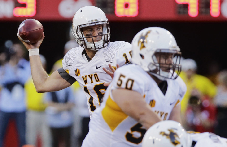 Photo - Wyoming quarterback Brett Smith, left, throws in the first half of an NCAA college football game against Nebraska on Saturday, Aug. 31, 2013, in Lincoln, Neb. (AP Photo/Nati Harnik)